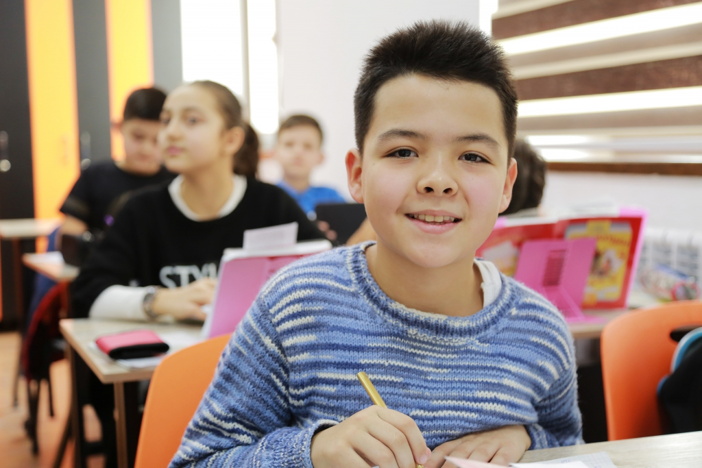 boy in blue and white striped long sleeve shirt holding pencil